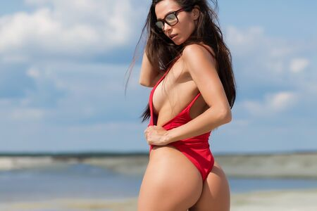 Photo pour Gorgeous tanned woman in sunglasses dressed in swimsuit standing on beach near sea looking at camera - image libre de droit