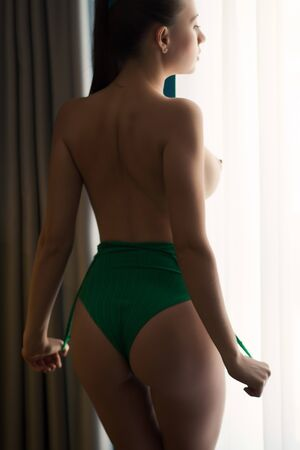 Photo pour Unrecognizable seductive female in thongs showing perfect bottom while standing near window at home - image libre de droit