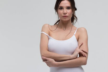 Photo for Alluring woman pulling strap of white t shirt and looking at camera - Royalty Free Image