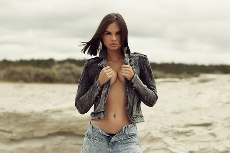 Photo pour Attractive female model in jeans looking at camera and covering breast with denim jacket on blurred background of countryside - image libre de droit