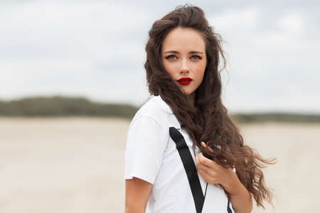 Photo pour Carefree stylish female with red lips and long hair standing near tree in green garden and looking away - image libre de droit