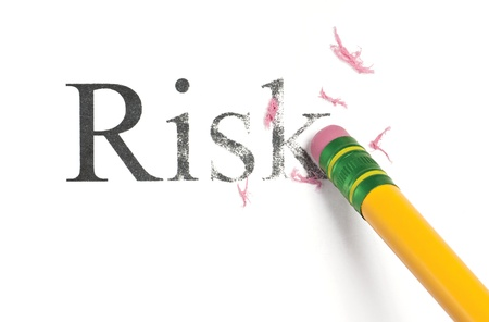 Close up of a yellow pencil erasing the word, 'Risk.' Isolated on white.