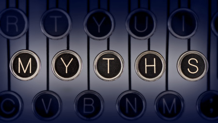 Close up of old manual typewriter keyboard with scratched chrome keys that spell out  MYTHS    Lighting and focus are centered on  MYTHS