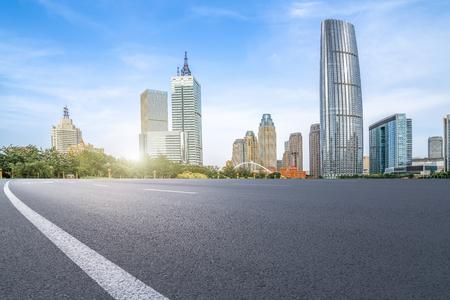 The empty asphalt road is built along modern commercial building