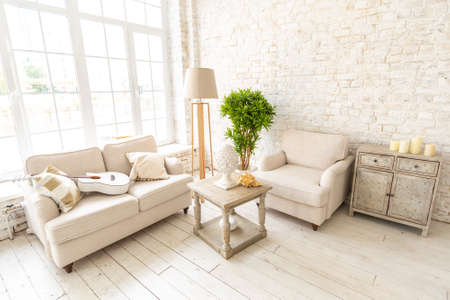 Foto de Large spacious room with a trendy loft design of sitting area. huge windows and stylish wicker light furniture inside. an abundance of ethnic decor - Imagen libre de derechos