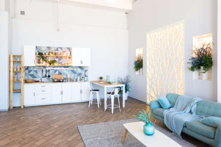 Foto de Fashionable spacious apartment with a stylish design in green, gray and white pastel colors with big window and decorative walls. bedroom and kitchen space - Imagen libre de derechos