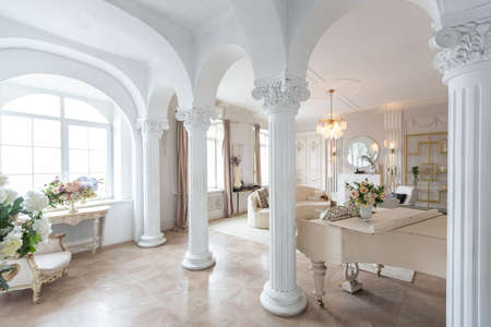 Photo for rich luxurious interior of a cozy room with modern stylish furniture nd grand piano, decorated with baroque columns and stucco on the walls - Royalty Free Image
