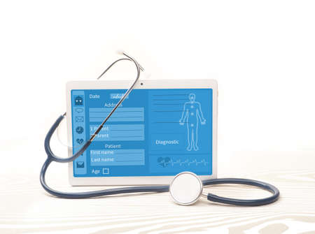 Photo pour White tablet and stethoscope on background. Online medical support concept. - image libre de droit