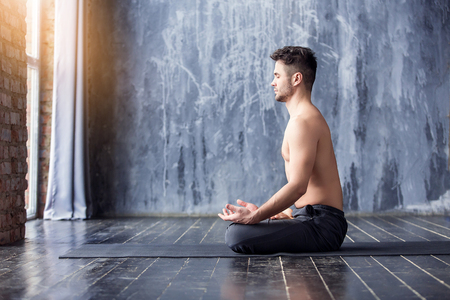 Photo pour Young caucasian yoga master smiling and looking at window. Yogi men sitting in lotus pose and meditates on dark urban background indoors. Yoga men workout in studio on black mat - image libre de droit