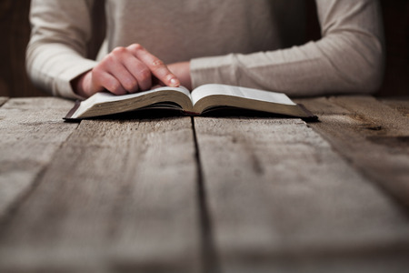 Photo pour woman hands on bible. she is reading and praying over bible in a dark space over wooden table - image libre de droit