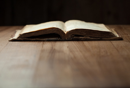 Image of an old Holy Bible on wooden background in a dark space
