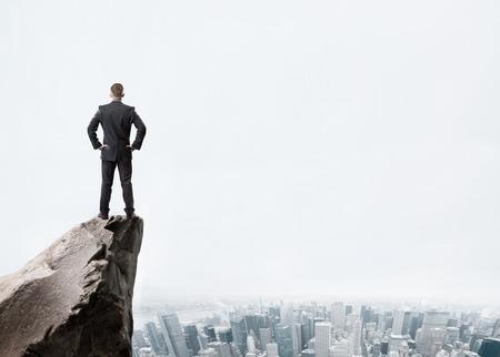 Foto de Young businessman standing on edge of rock mountain and looking at the city - Imagen libre de derechos