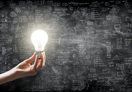 Foto de hand holding or showing a light bulb in front of  business idea concept on wall backboard blackground - Imagen libre de derechos
