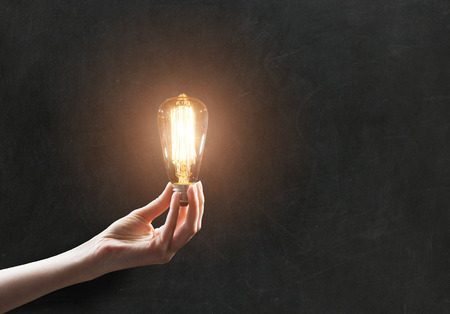 hand holding Light bulb on blackboard background