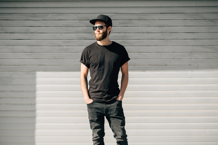 Photo pour Hipster handsome male model with beard  wearing black blank  t-shirt with space for your logo or design in casual urban style - image libre de droit