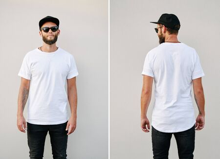 Photo pour Hipster handsome male model with beard wearing white blank t-shirt and a baseball cap with space for your logo or design in casual urban style. Back and front view - image libre de droit