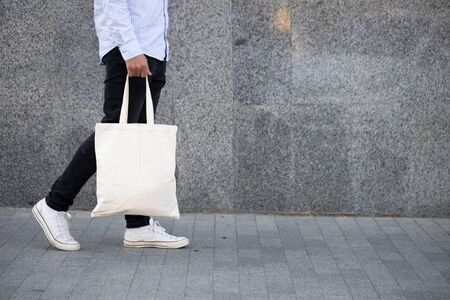 Photo for Young man holding white textile eco bag against urban city background. Ecology or environment protection concept. White eco bag for mock up. - Royalty Free Image