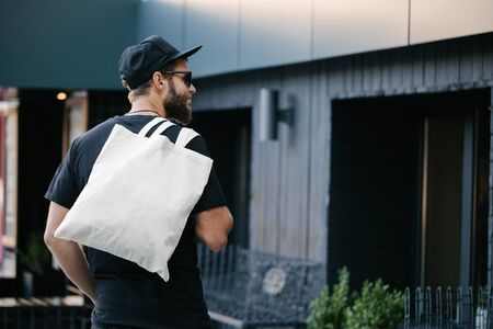 Photo pour Young man holding white textile eco bag against urban city background. Ecology or environment protection concept. White eco bag for mock up. - image libre de droit