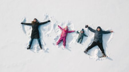 Foto per Family making a snow angel. Aerial view. Mother and father and chilren making a snow angel - Immagine Royalty Free
