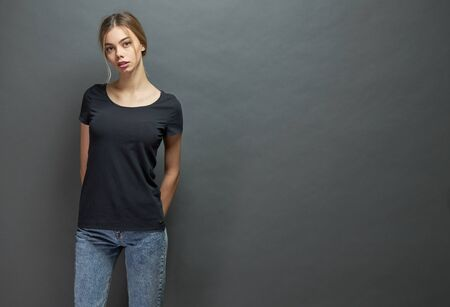 Photo pour Sexy woman or girl wearing black blank t-shirt with space for your logo, mock up or design in casual urban style over gray background - image libre de droit