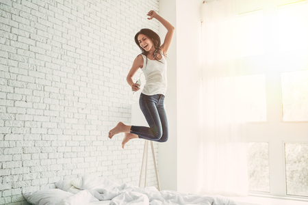 Photo pour Happy young woman in earphones is listening to music with smart phone, jumping on bed, singing and smiling - image libre de droit