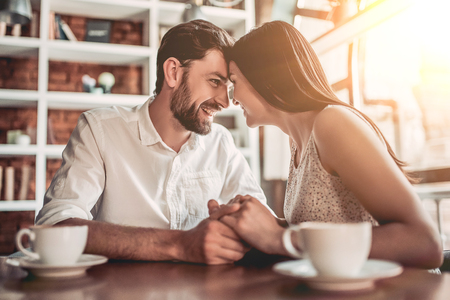 Couple in love is sitting in cafe face to face, holding hands and smiling