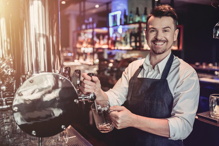 Photo pour Cheerful bartender on a bar counter is working and smiling. - image libre de droit