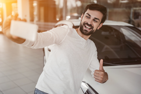 Young man is choosing a new vehicle in car dealership and making photo on a smartphone.