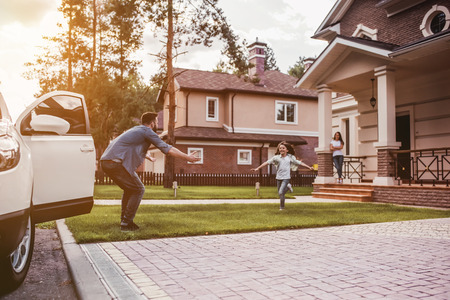 Foto de Happy family. Dad came home, daughter is running to meet him while wife is waiting on the house's porch. - Imagen libre de derechos