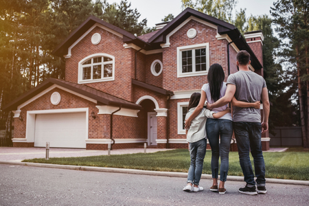 Photo for Back view of happy family is standing near their modern house and hugging - Royalty Free Image