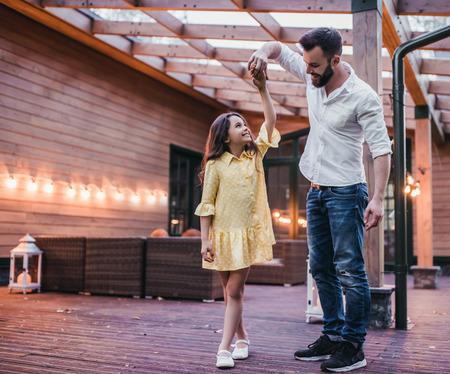 Foto de Dad is dancing with his daughter on house's terrace. - Imagen libre de derechos