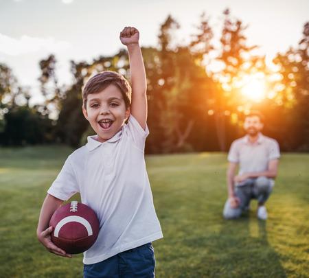 Foto de Handsome dad with his little cute sun are having fun and playing American football on green grassy lawn - Imagen libre de derechos
