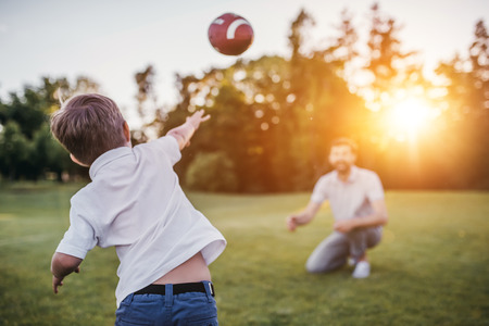 Handsome dad with his little cute sun are having fun and playing American football on green grassy lawn
