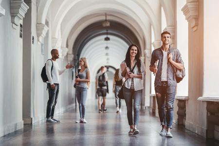 Foto de Multiracial students are walking in university hall during break and communicating. - Imagen libre de derechos