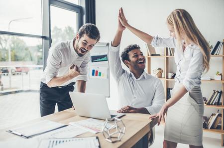 Foto de Group of happy young multiracial people working in modern light office. Businessmen at work. Feeling of success - Imagen libre de derechos