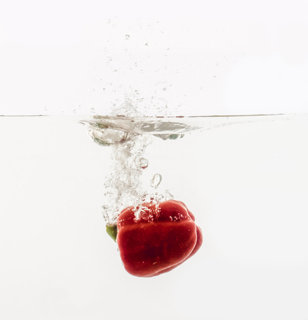 Vegetables are thrown into the water in transparent vessel. Red Bulgarian pepper and water splash on white background.