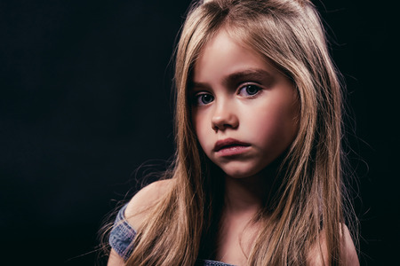 Portrait of little cute girl with long hair is posing on black background. Charming blonde isolated.