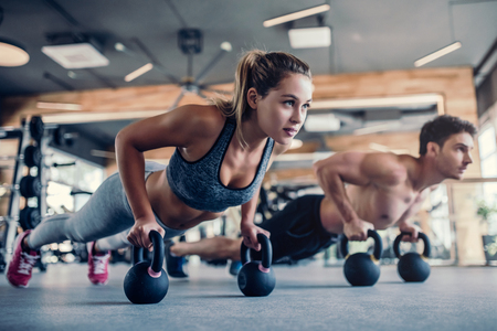 Foto de Young couple is working out at gym. Attractive woman and handsome muscular man are training in light modern gym. Doing plank on kettlebell. Push-up on weights. - Imagen libre de derechos
