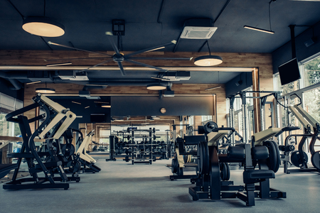 Foto de Modern light gym. Sports equipment in gym. Barbells of different weight on rack. - Imagen libre de derechos