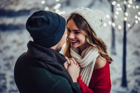 Young romantic couple is having fun outdoors in winter before Christmas. Enjoying spending time together in New Year Eve. Two lovers are hugging and kissing in Saint Valentine's Day.
