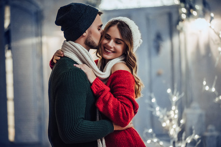 Foto de Young romantic couple is having fun outdoors in winter before Christmas. Enjoying spending time together in New Year Eve. Two lovers are hugging and kissing in Saint Valentine's Day. - Imagen libre de derechos