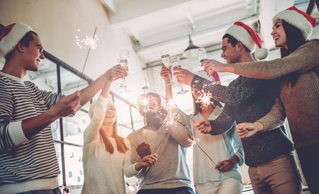 Foto de Merry Christmas and Happy New Year 2018!Multiracial young creative people are celebrating holiday in modern office. - Imagen libre de derechos