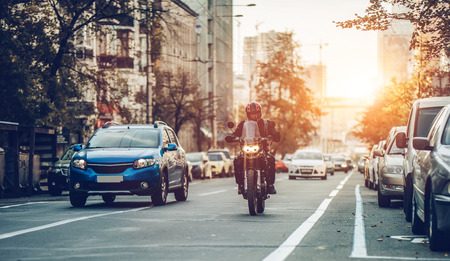 Foto de Motorcycle and cars are riding on street. City during the sunset. - Imagen libre de derechos