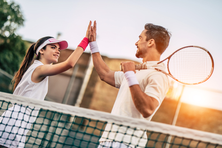 Foto de Young couple on tennis court. Handsome man and attractive woman are playing tennis. Giving five. - Imagen libre de derechos