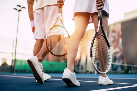 Cropped image of young couple on tennis court. Handsome man and attractive woman are playing tennis.