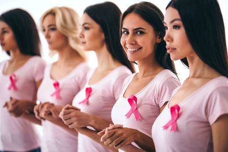 Foto de Group of young multiracial woman with pink ribbons are struggling against breast cancer. Breast cancer awareness concept. - Imagen libre de derechos