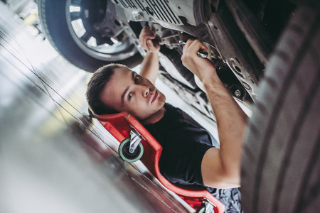 Photo pour Handsome mechanic in uniform is working in auto service with wrenches. Man on portable plastic repair creeper. Car repair and maintenance. - image libre de droit