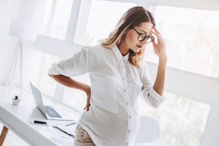 Attractive pregnant woman is working in light modern office. Feel of tiredness and headache on last months of pregnancy.