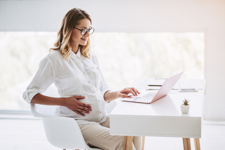 Photo for Attractive pregnant woman is working with laptop in light modern office. Last months of pregnancy. - Royalty Free Image