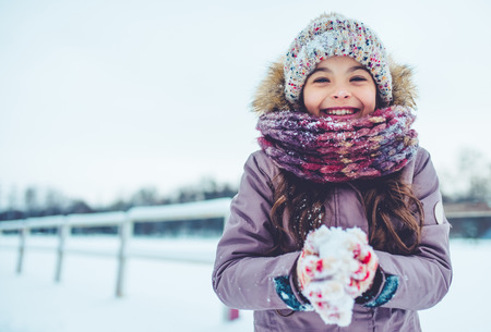 Foto de Little cute girl is having fun outdoots in winter. - Imagen libre de derechos